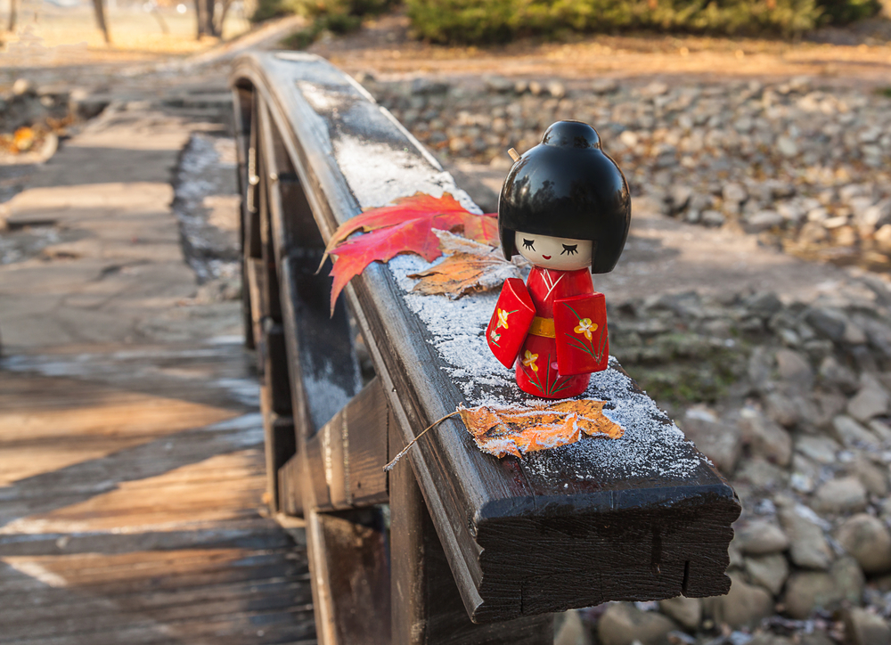 Japanese wooden doll Kokeshi on the background of maple leaves with frost. Concept season maple leaves Momiji-gari.